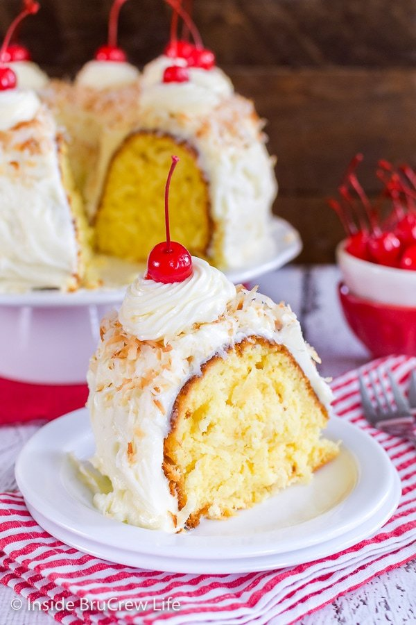 A white plate on a red and white striped towel with a slice of pina colada bundt cake on it and more cake behind it