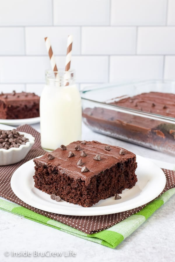 A white plate with a slice of chocolate zucchini brownies topped with chocolate frosting.