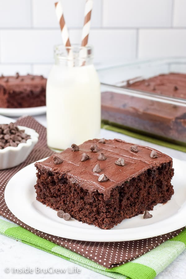 A white plate with a slice of zucchini brownies topped with chocolate frosting.