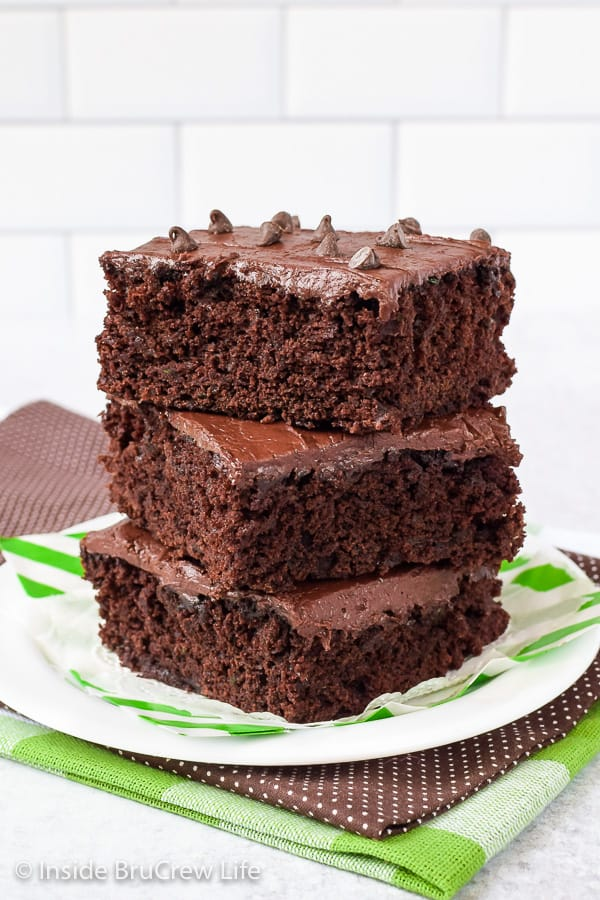 A white plate with three frosted zucchini brownies stacked on it.