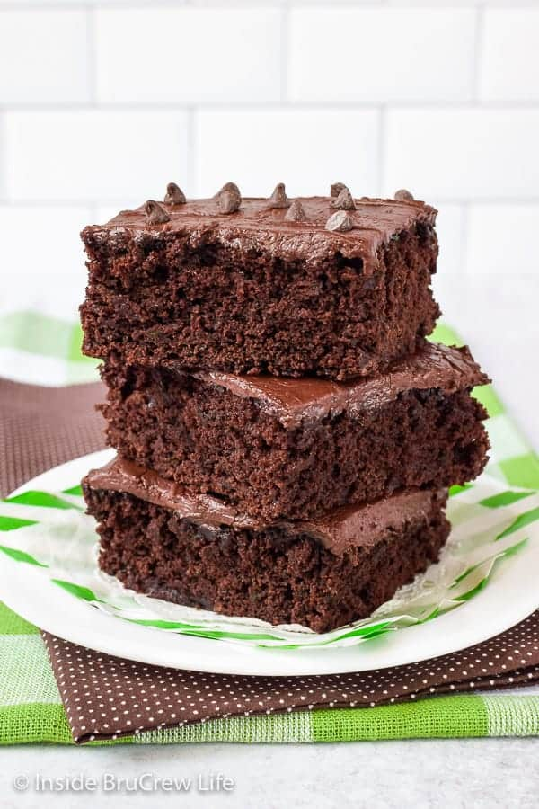 Frosted Zucchini Brownies - these soft homemade brownies get their fluffy and rich texture from shredded zucchini and dark cocoa powder. Make this easy recipe with the extra veggies you have from your garden. #brownies #darkchocolate #zucchini #chocolatefrosting
