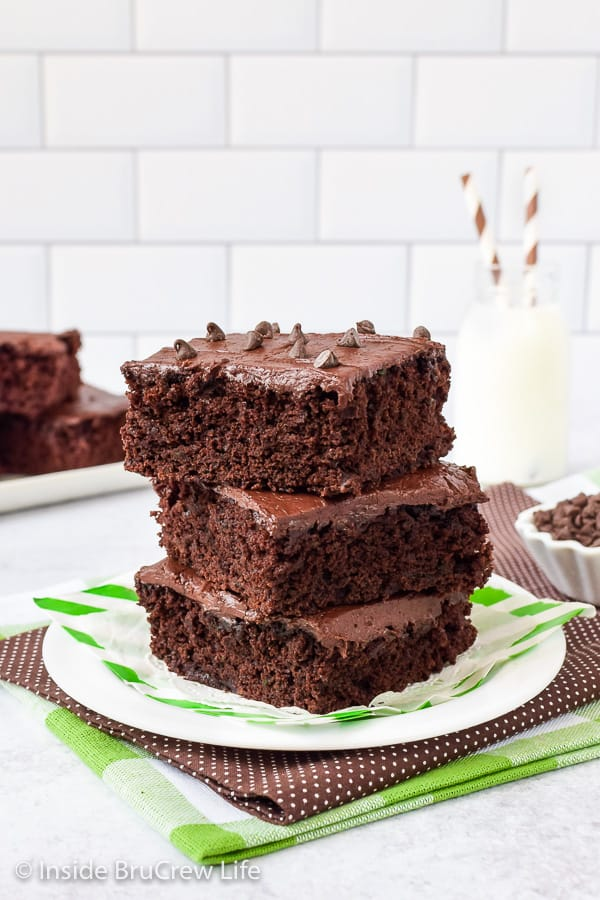 A white plate with three frosted zucchini brownies stacked on it and glass of milk behind it.