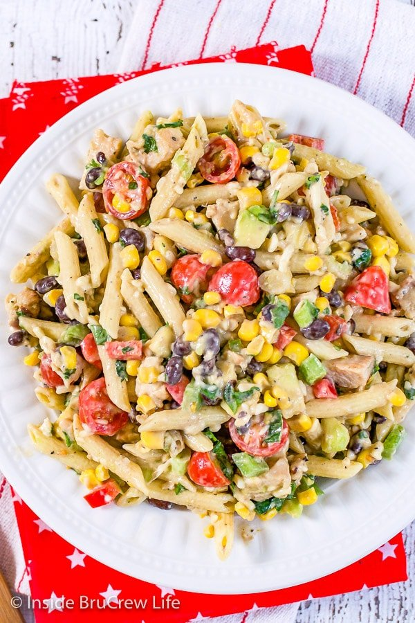 A large white bowl on a red towel filled with a southwest ranch pasta salad