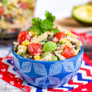 A blue bowl filled with ranch pasta salad loaded with veggies