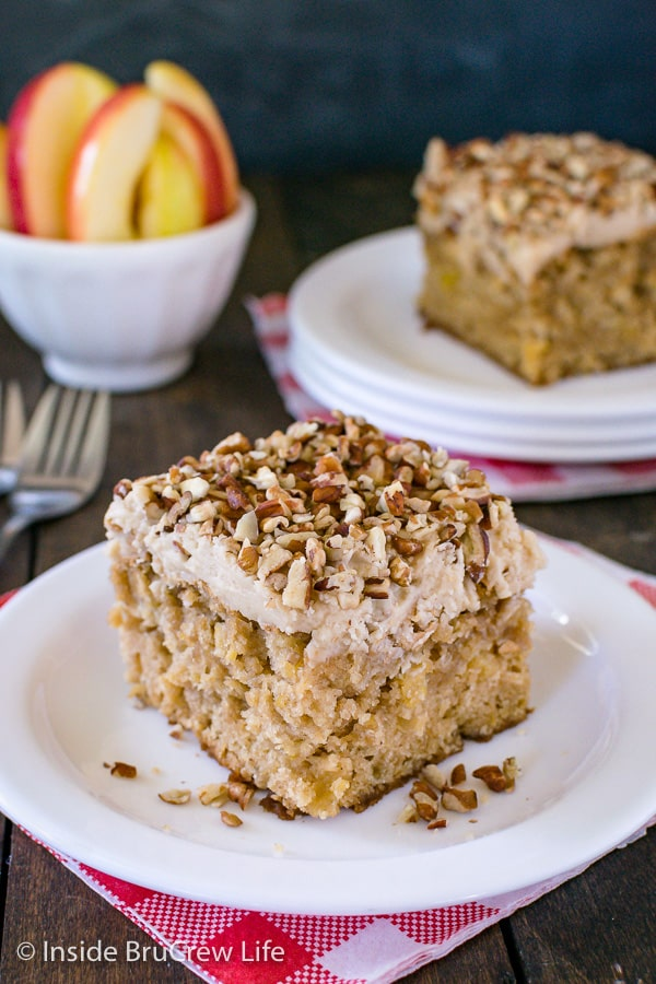 A white plate with a piece of apple praline cake topped with frosting and pecans on it