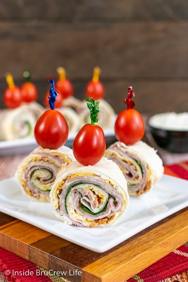 Three turkey club pinwheels topped with cherry tomatoes on a white plate