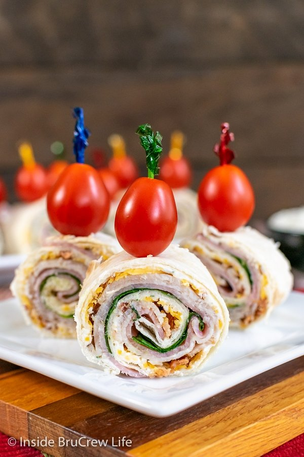 A white plate with three turkey club pinwheels standing up with a toothpick and cherry tomato