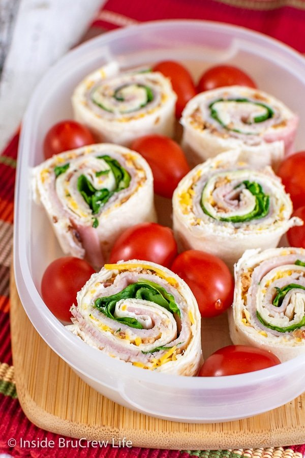 Turkey Club Pinwheels in a clear plastic container with cherry tomatoes