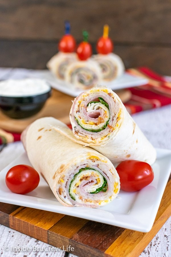 A turkey club pinwheel cut in half and stacked on a white plate