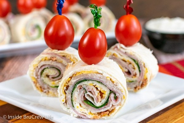 Three turkey club pinwheels on a white plate topped with a toothpick and cherry tomato
