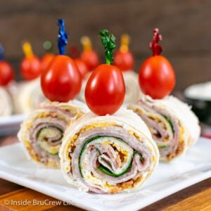 Three turkey club pinwheels on a white plate topped with tomatoes