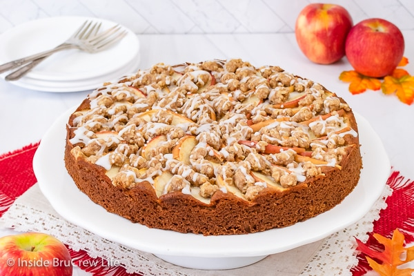 A white cake plate with a full apple crumble cake with a sweet glaze on it.