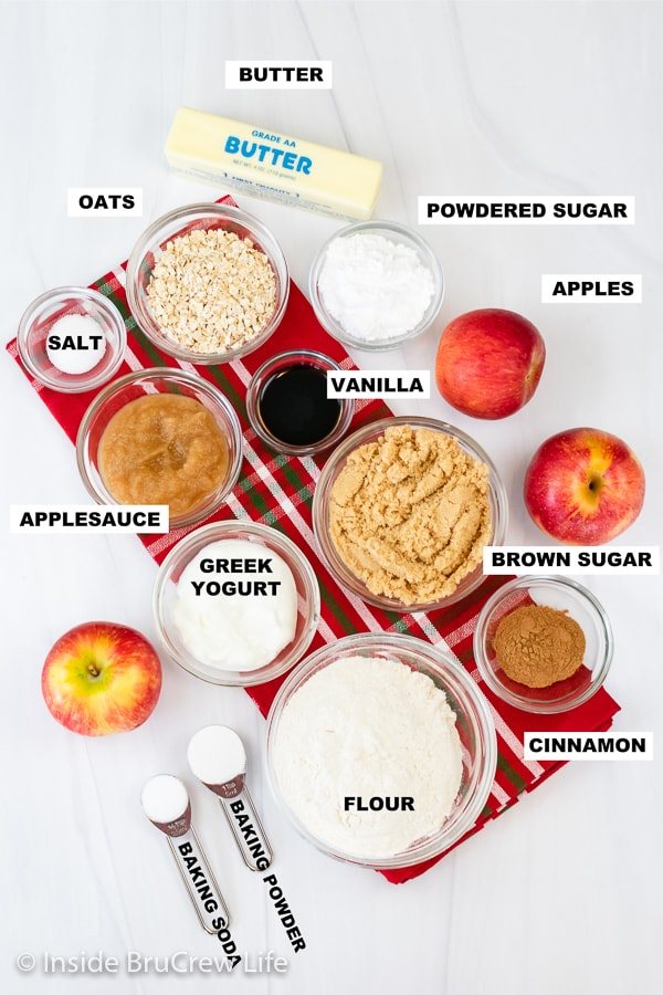 A white board with bowls of ingredients needed to make an apple crumble coffee cake.