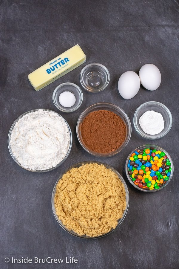 Bowls of ingredients needed to make M&M brownies on a black board.