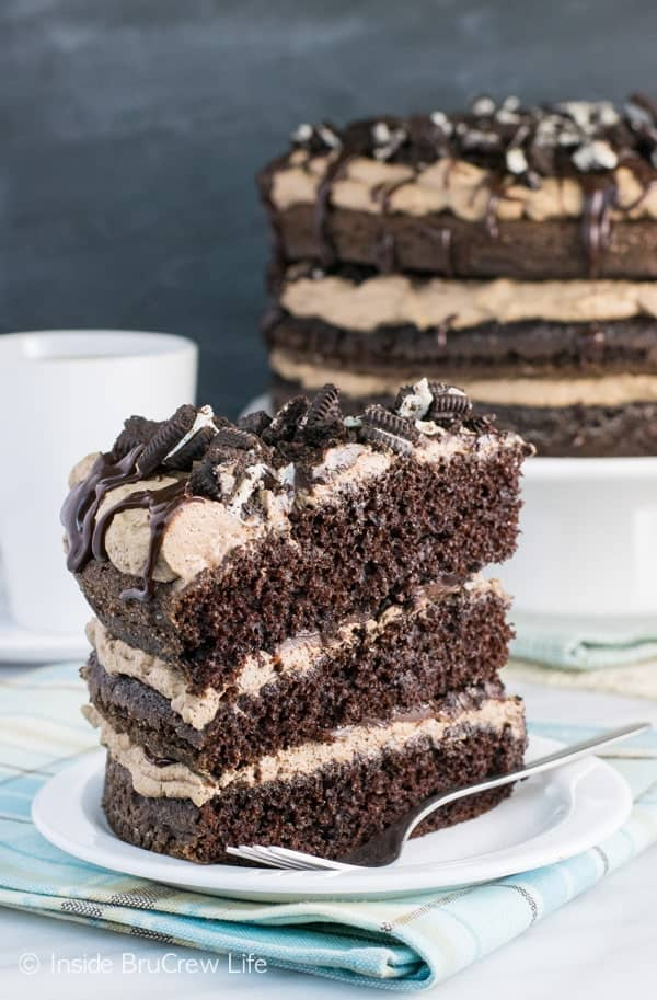 A white plate with a slice of mississippi mudslide cake topped with oreos and fudge and the rest of the cake behind it