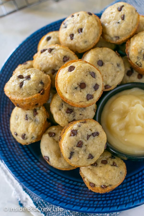 Overhead picture of mini pancake muffins on a blue plate with a bowl of honey butter