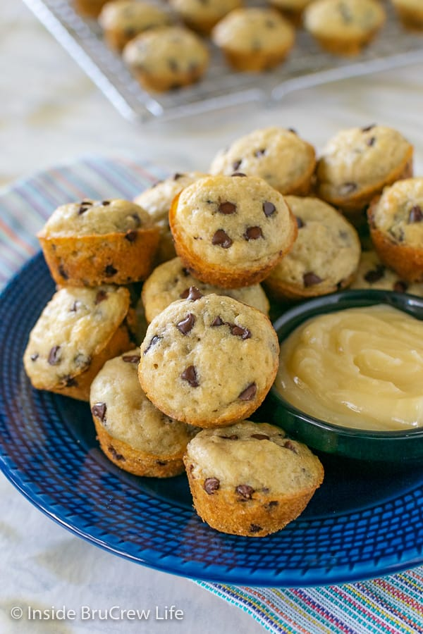 A blue plate filled with mini pancake muffins and a bowl of honey butter