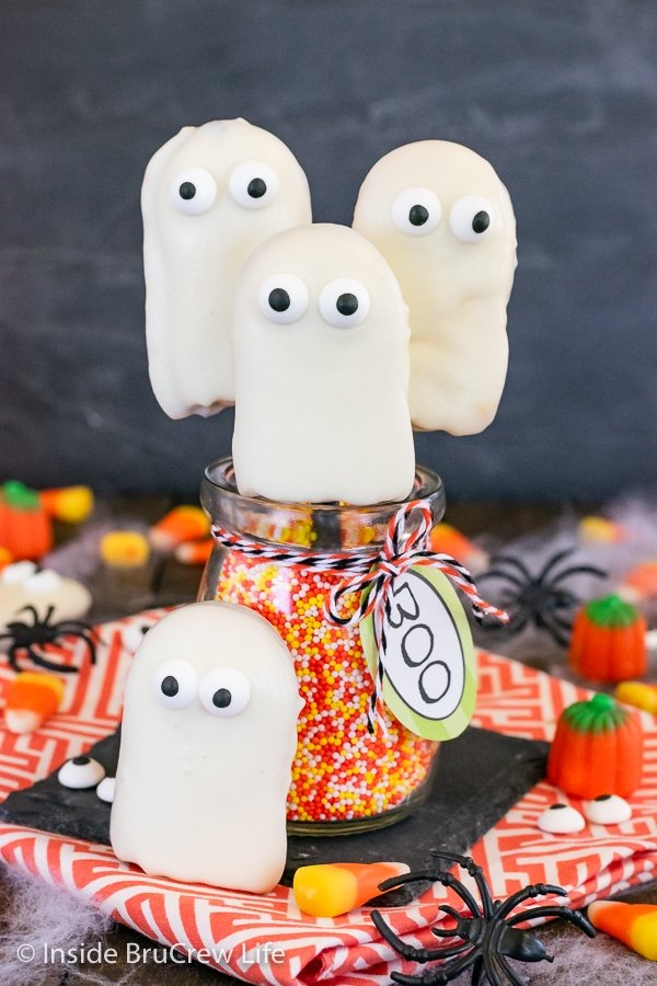 Three ghost cookies with candy eyeballs attached to straws and stuck in a jar of sprinkles.