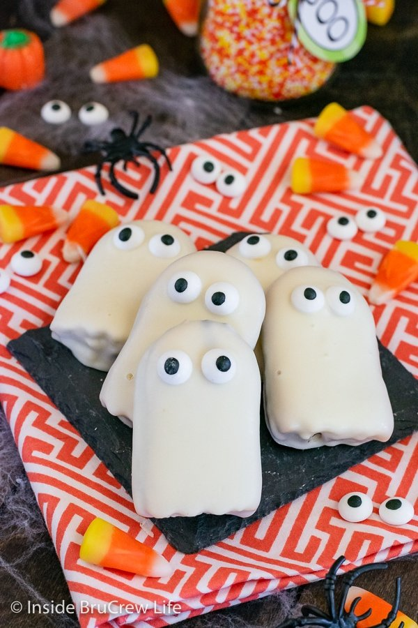 Ghost cookies with candy eyes lying on an orange and white towel.