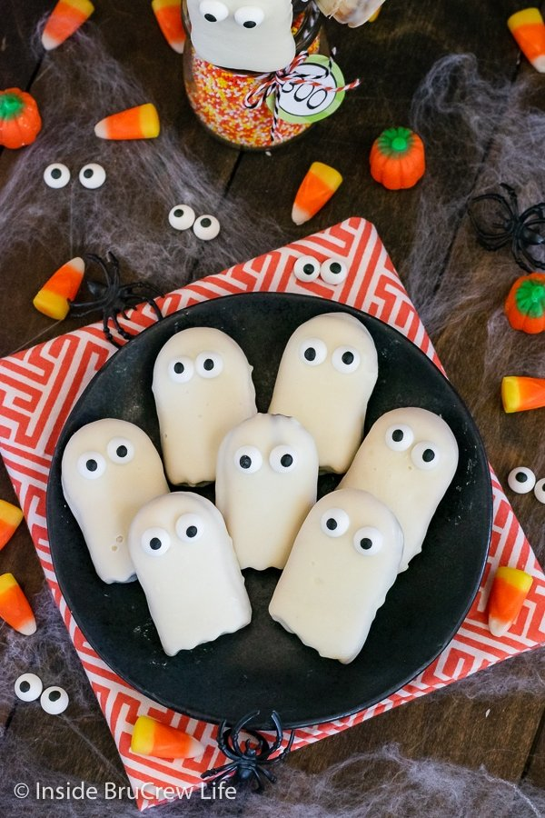 A black plate with ghost cookies with candy eyes stacked on it.