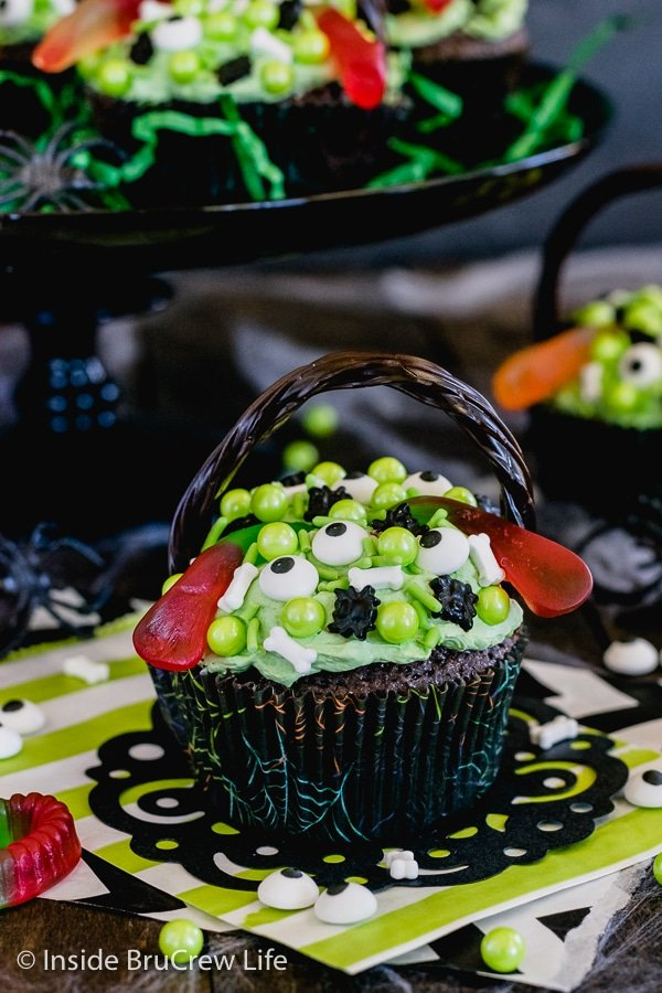 Brownie cupcake topped with green frosting and spooky sprinkles on a black doily with more cupcakes behind it