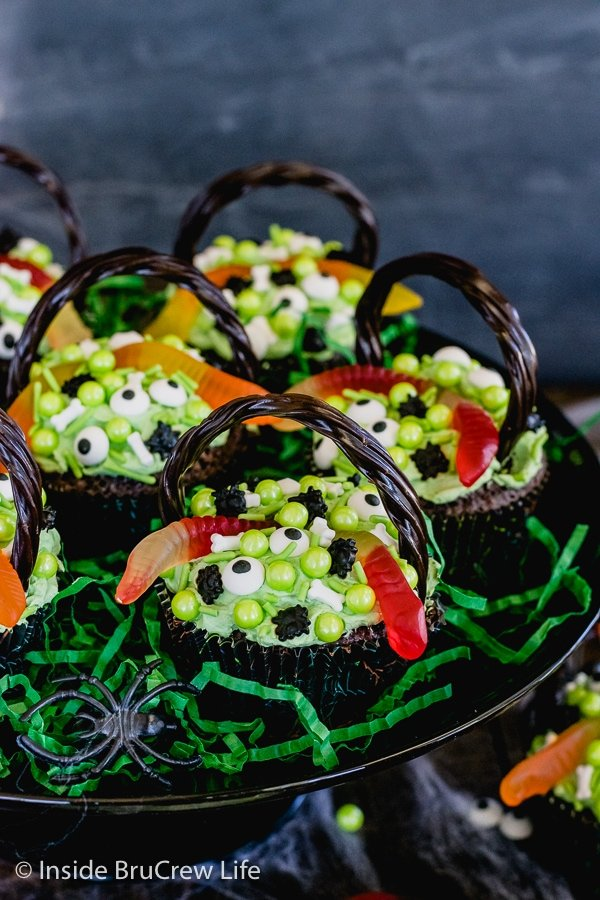 A black cake plate with brownie cupcakes topped with green frosting and spooky candies on it
