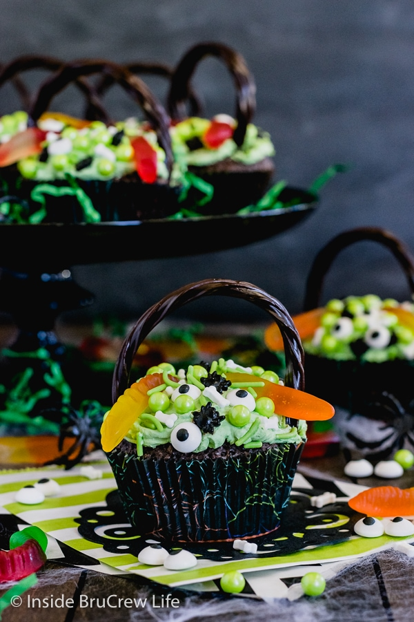 A brownie cupcake decorated with green frosting and spooky candies to look like a witch's cauldron with more cupcakes behind it