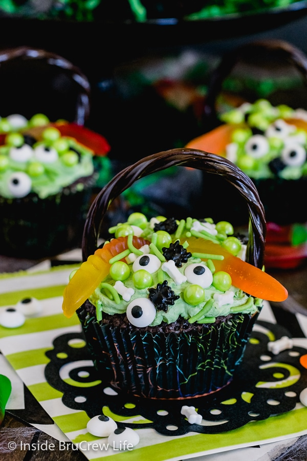 A close up picture of a brownie cupcakes topped with green frosting, gummy worms, and spooky sprinkles to look like a witch's cauldron