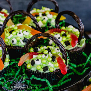 A black cake stand with brownie cupcakes decorated with candies and gummy worms to look like witch cauldrons