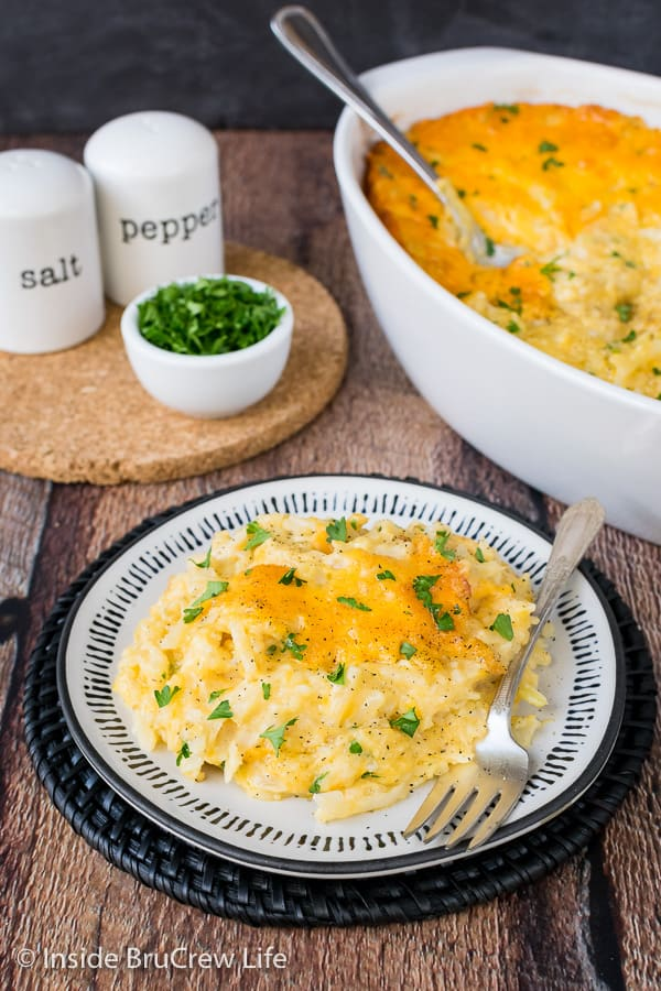 A white casserole dish with cheesy hashbrown casserole in it and a white plate with a serving of potatoes on it too