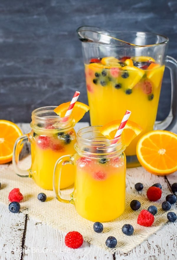 Pineapple Orange Punch - mix together fruit juice, Sprite, and fresh berries for an easy kid friendly drink to serve at parties. Easy recipe to mix together! #nonalcoholicpunch #partypunch #fruitjuice #kidfriendlydrinks #punch #recipe