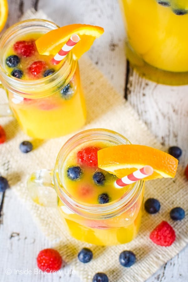 Pineapple Orange Punch - float fresh berries in fruit juice mixed with Sprite for an easy party punch! Try this recipe for any kind of party! #nonalcoholicpunch #partypunch #fruitjuice #kidfriendlydrinks #punch #recipe