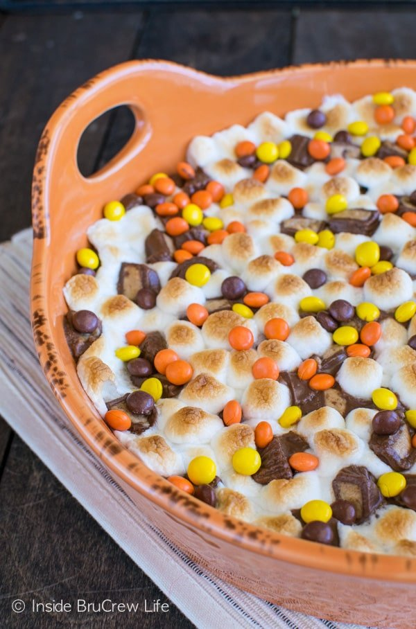 Adding a s'mores twist to peanut butter cookie dough and candy makes this Reese's S'mores Cookie Pizza amazing! Great dessert recipe!