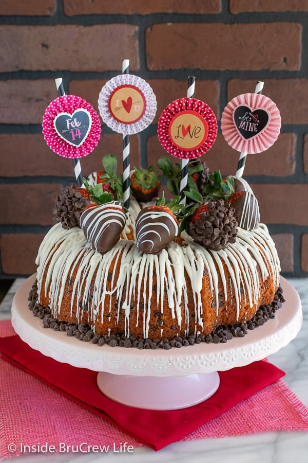 A full sized Strawberry Chocolate Chip Bundt Cake on a pink cake plate with paper straws and flag decorations on top