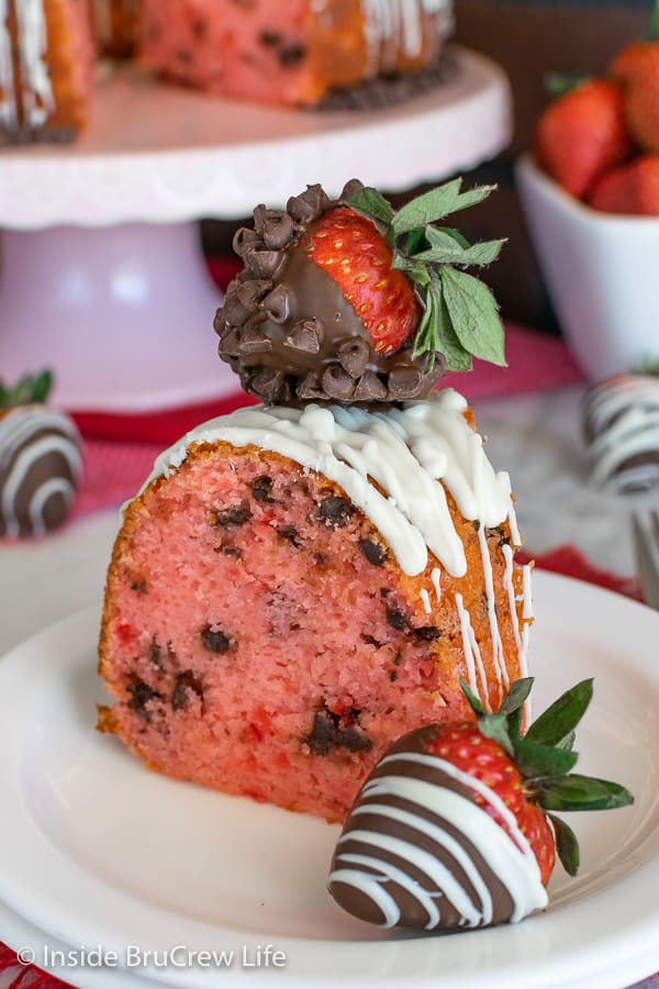 Close up of slice of strawberry chocolate chip bundt cake with chocolate covered strawberries
