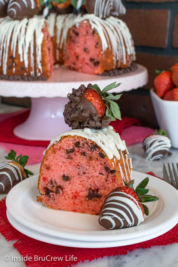A white plate with a slice of strawberry chocolate chip bundt cake with chocolate covered strawberries and the cake behind it