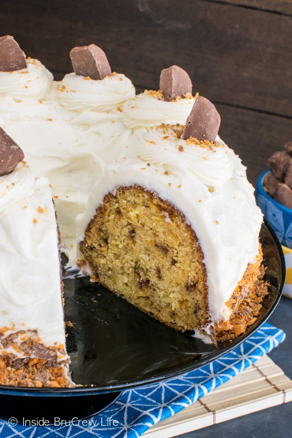 Swirls of frosting and candy bars give this Banana Butterfinger Bundt Cake a fun twist. Delicious dessert recipe.