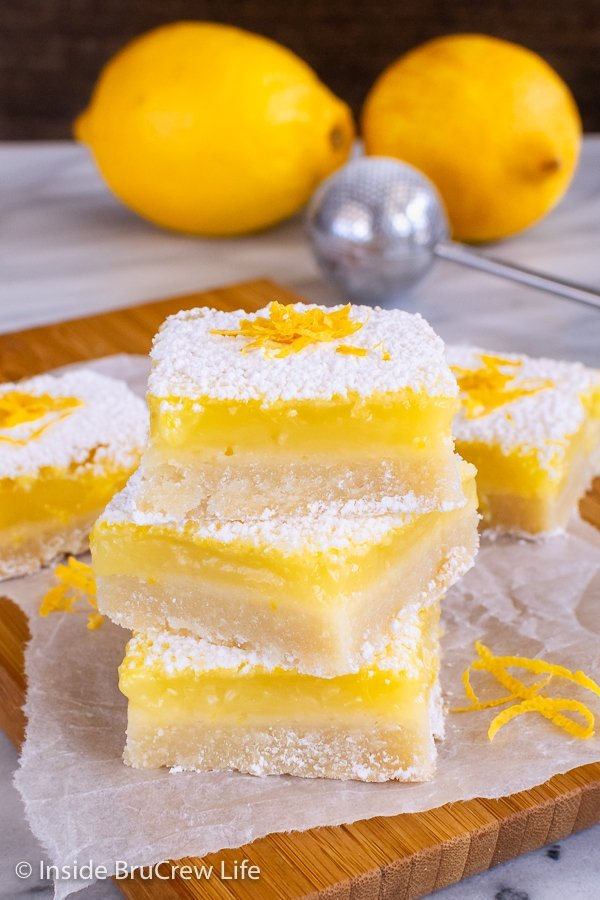 A stack of three lemon bars with powdered sugar on a wooden board with lemons behind it