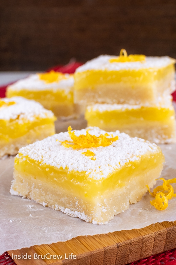 Squares of easy lemon bars with powdered sugar on top on a wooden cutting board
