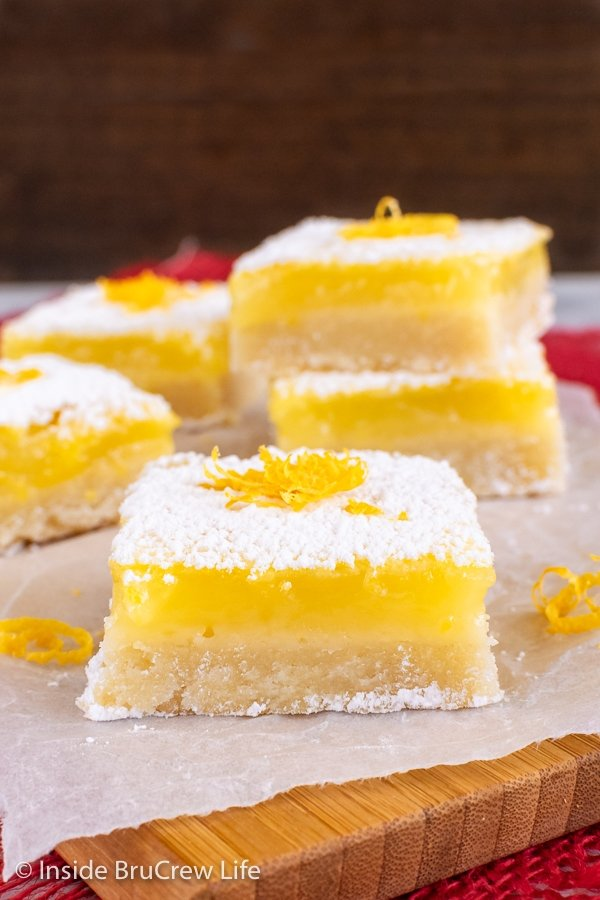 Squares of easy lemon bars with powdered sugar on a wooden cutting board