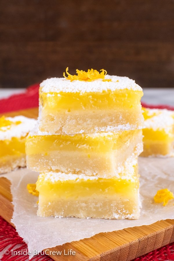 Three lemon bars with powdered sugar stacked on top of each other on a wooden cutting board