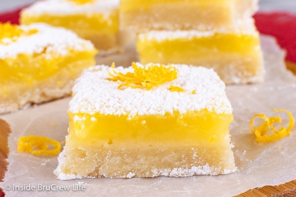 A close up of a lemon bar topped with powdered sugar and lemon zest