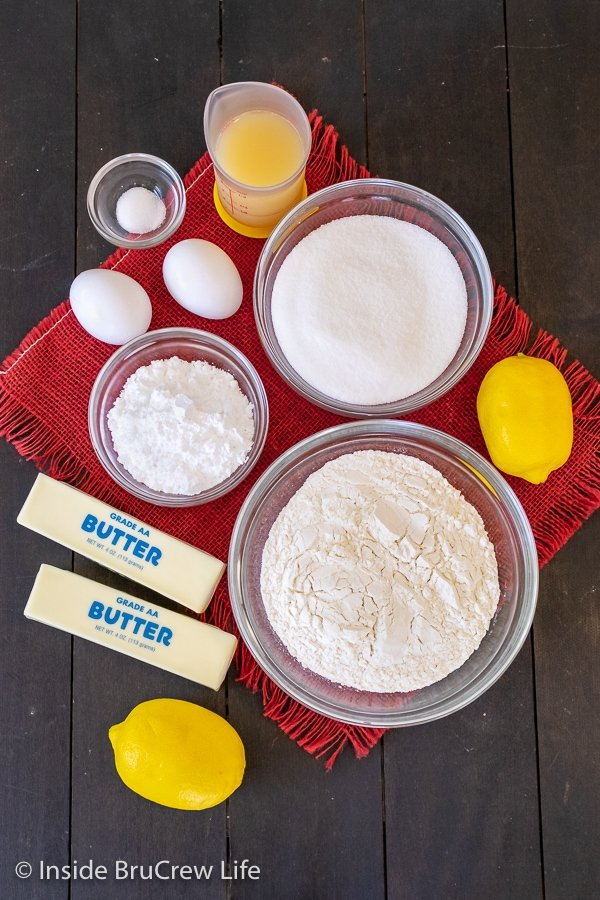 A wooden board with bowls of ingredients to make easy lemon bars on it