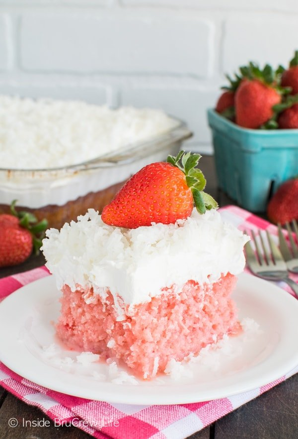 This easy Strawberry Coconut Poke Cake is filled with 2 kinds of milk and frosted with a creamy topping and coconut. Great dessert recipe for spring or Easter.