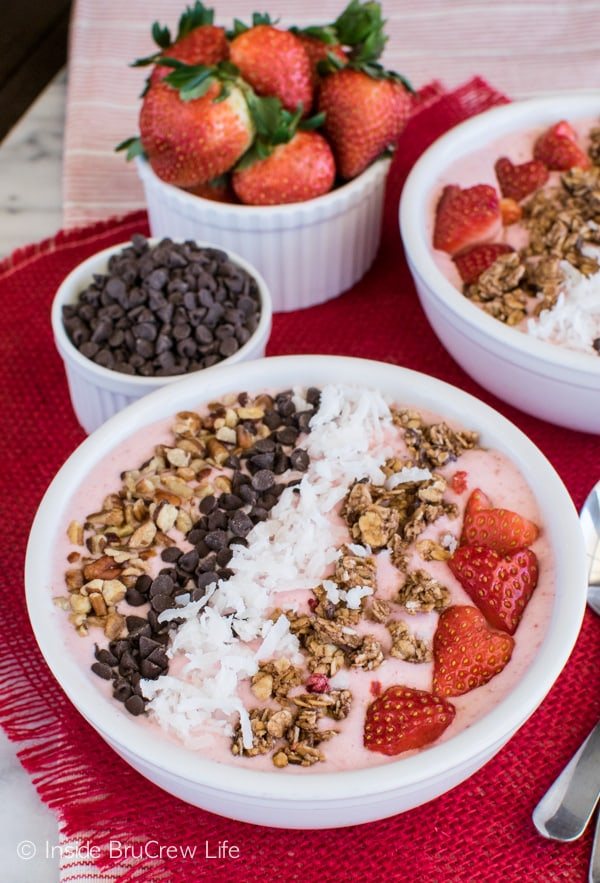 Strawberry Coconut Smoothie Bowl recipe - easy strawberry smoothie topped with nuts, chocolate, berries, and coconut. It's a delicious breakfast or snack option.
