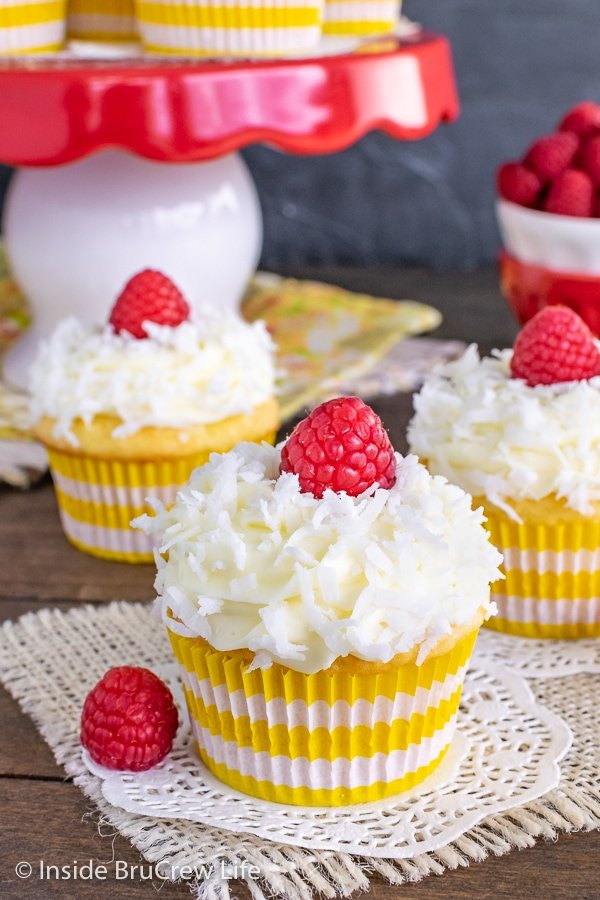 Three coconut cupcakes with yellow and white liners topped with lemon frosting, shredded coconut, and a raspberry on a wooden board