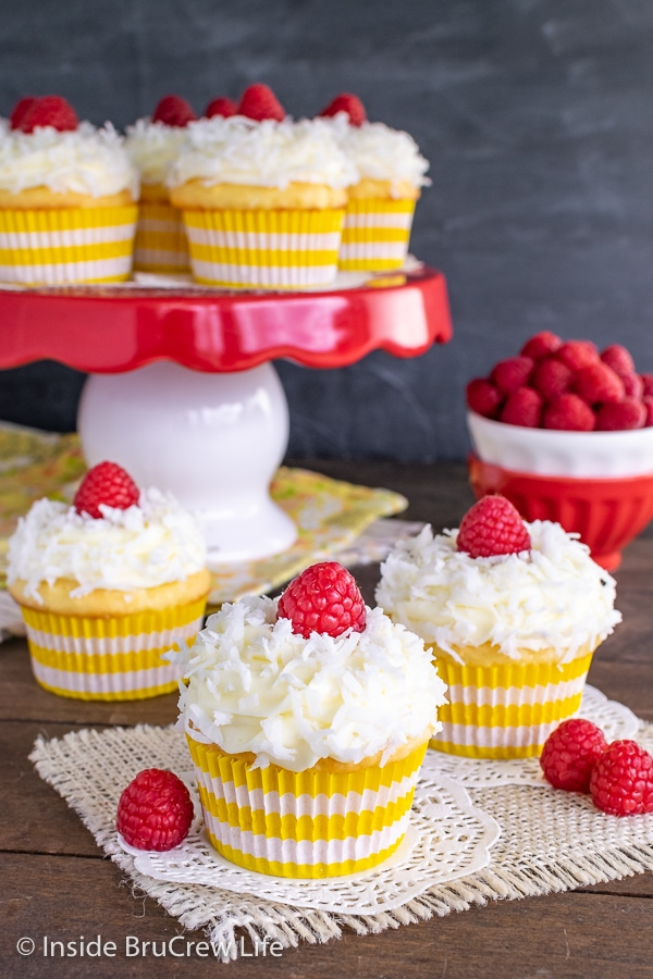 Three lemon coconut cupcakes topped with shredded coconut and raspberries on a wooden board and a cake plate with more cupcakes behind them.