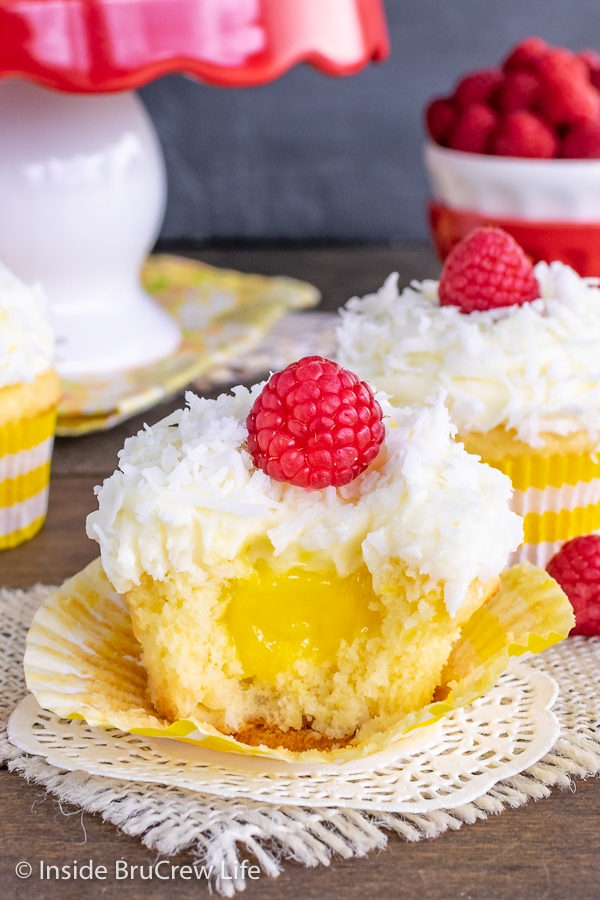 A coconut cupcake with lemon frosting and a raspberry with a bite taken out showing the hidden lemon pie filling center