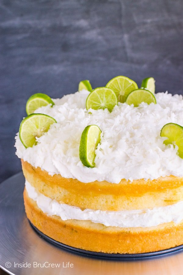 Coconut Key Lime Rum Cake - a sweet coconut frosting and a rum glaze give this easy key lime cake a fun blast of flavor. Make this easy recipe for spring parties! #keylime #rumcake #coconut #layercake #cake #doctoredcakemix