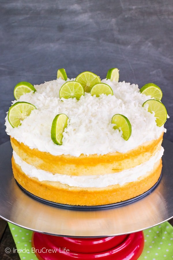 Coconut Key Lime Rum Cake - fluffy coconut frosting and a sweet rum glaze gives this key lime cake so much flavor. Try this easy recipe for spring and summer parties! #keylime #rumcake #coconut #layercake #cake #doctoredcakemix
